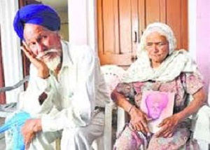 Kuldip Singh's mother holds his picture as father Ajaib Singh looks on at Amrali village in Ropar.