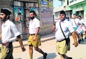 RSS activists brandish firearms during a street march in Faridkot's Jaitu town on Oct. 05, 2014