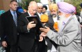 A survivor of the 1984 massacres hands over a copy of Sikh Genocide 1984 Report to Gov. Jerry Brown